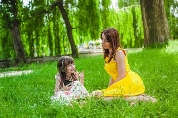 少女の音楽に耳を傾け、彼女の母親は彼女を見て