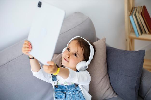 Маленькая девочка слушает музыку через наушники