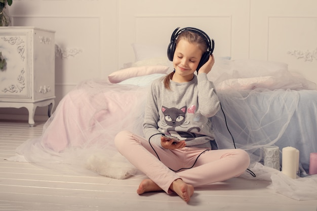 The little girl listens to music in the room.