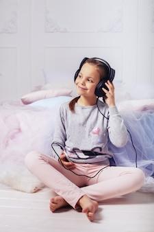 Little girl listens to music through headphones