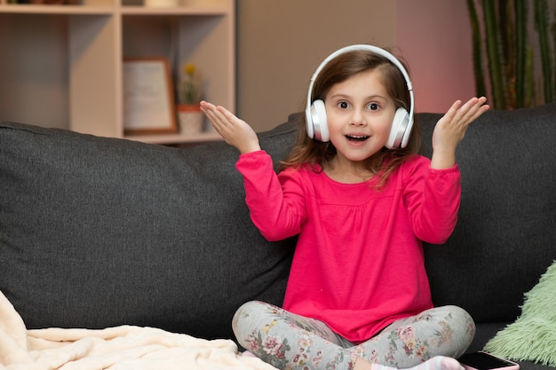 Little girl listens to music on wireless headphones. funny little girl dancing, singing and moving to rhythm. kid wearing headphones.