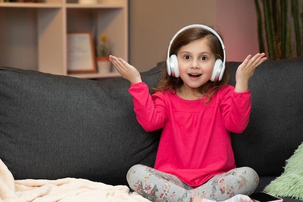 어린 소녀는 무선 헤드폰에서 음악을 듣습니다. 춤, 노래 및 리듬으로 이동 재미있는 작은 소녀. 헤드폰을 착용하는 아이.