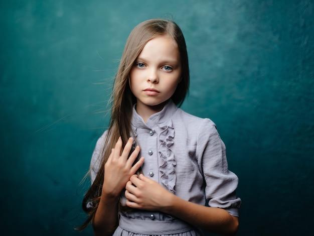격리 된 배경 포즈 드레스에 어린 소녀 긴 머리