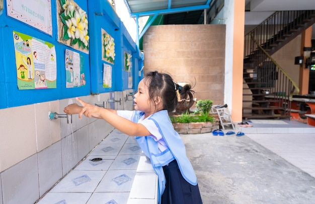 Little girl look news while wash her hands before eating at school