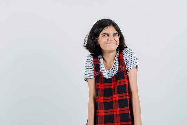 ピナフォアの服を着て脇を見て恥ずかしそうに見える少女、