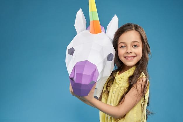 Маленькая девочка смотрит в камеру и держит бумажного единорога