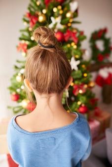 크리스마스 트리를 보는 어린 소녀