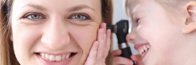 耳鏡で女医の耳を見ている少女。子供の概念における耳の病気の検査と治療