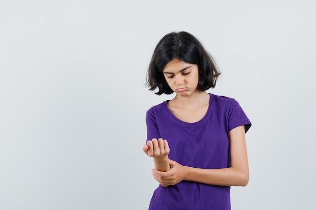 Tシャツを着て腕を見て悲しそうな少女。