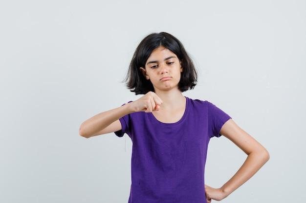 Tシャツでくいしばられた握りこぶしを見て自信を持って見ている少女、