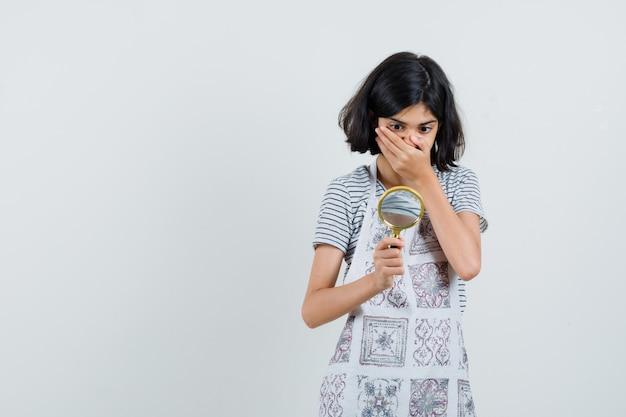 Tシャツ、エプロンで拡大鏡を見て驚いて見える少女、