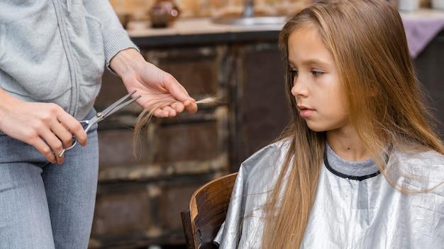 Маленькая девочка смотрит на волосы, вырезанные парикмахером