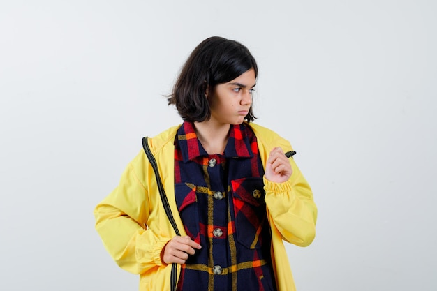チェックのシャツ、ジャケットで目をそらし、集中して見える少女。正面図。