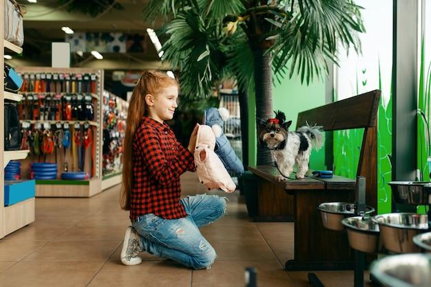 ペット ショップで犬の服を探している少女。ペットショップで子供を買う道具、家畜のアクセサリー