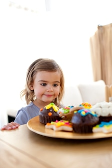 Little girl looking at confectionery at home