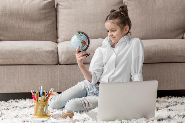 Bambina che esamina un globo della terra