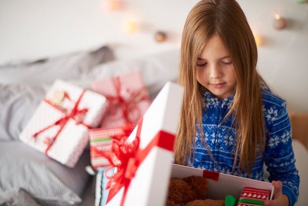 Bambina che osserva all'interno del regalo di natale