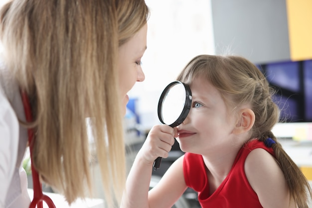 Little girl looking at pediatrician doctor with magnifier in clinic. correction of vision in children concept