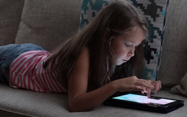 Little girl looking at the screen of a tablet on sofa