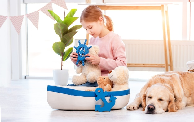 Little girl looking at steering wheel toy and golden retriever dog sleeping close to her