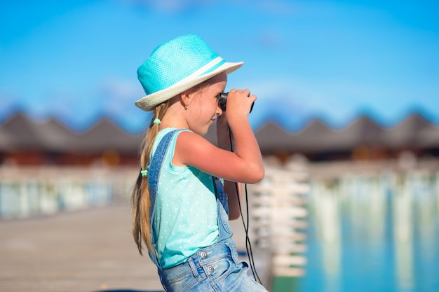 Little girl looking through binoculars in sunny day during summer vacation