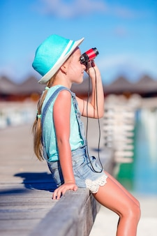 Little girl looking through binoculars in sunny day