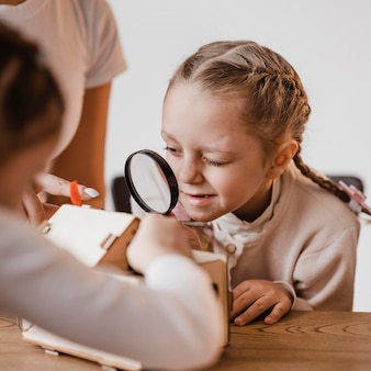 Little girl looking through a magnifier at an electrical device