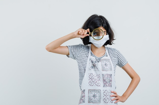 Маленькая девочка смотрит через увеличительное стекло в футболке, фартуке