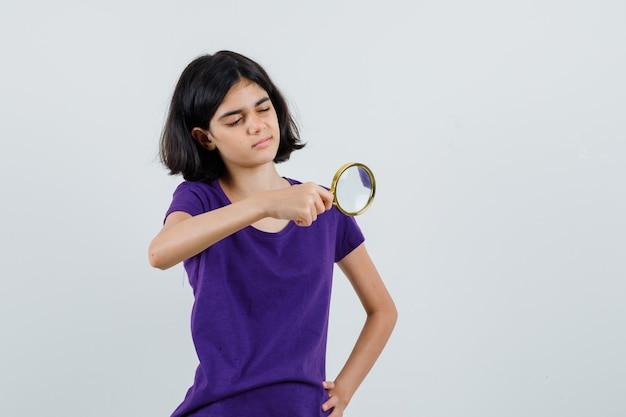 Tシャツの虫眼鏡を通して見ている少女