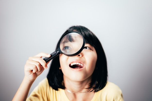 A little girl looking through a magnifying glass