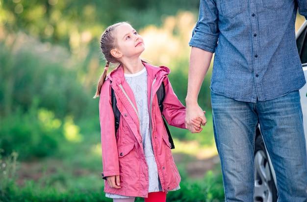 学校に行く前に父親を見上げる少女