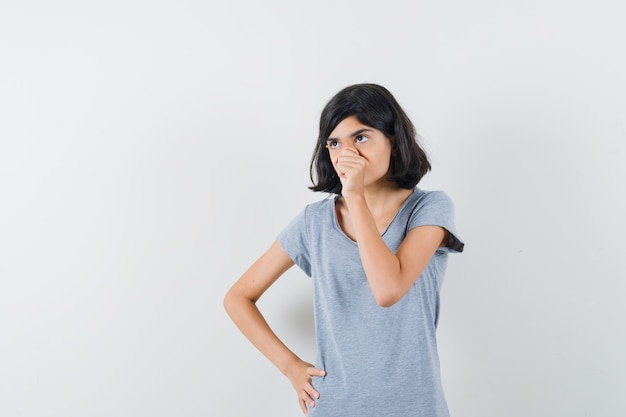 Bambina che osserva in su in maglietta e che sembra pensieroso. vista frontale.