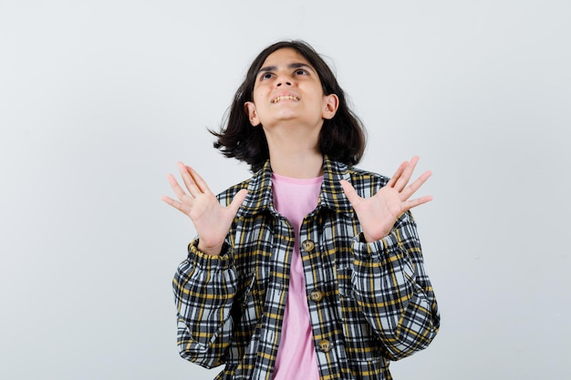 Little girl looking up while raising hands in shirt,jacket and looking aggressive , front view.
