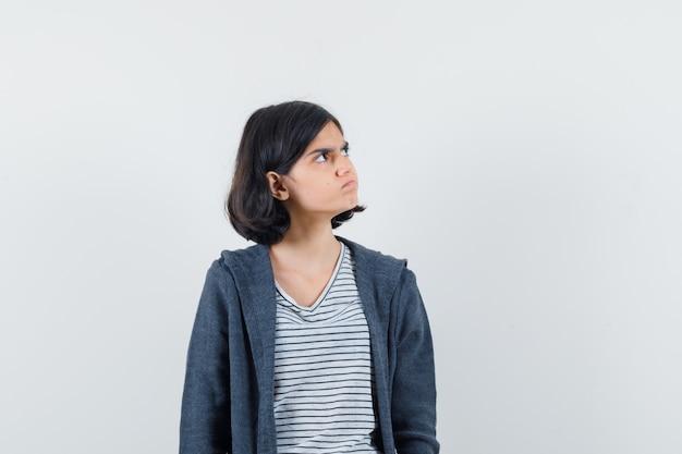 Tシャツ、ジャケットで上向きに見て物思いにふける少女