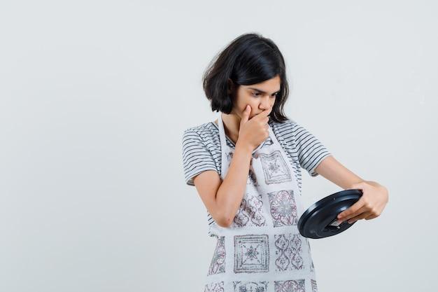 Bambina guardando l'orologio da parete in t-shirt, grembiule e guardando smemorato.