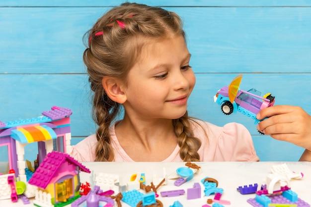 Маленькая девочка смотрит на небольшой автомобиль, собранный из конструктора.