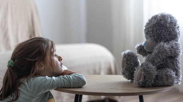 小さな女の子は、ぼやけた背景のコピースペースでお気に入りのおもちゃを持った子供であるテディベアを見ます。