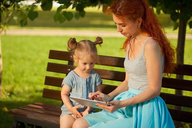 少女は母親と一緒にタブレットを見る