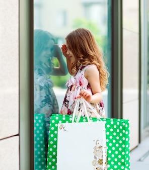 Маленькая девочка смотрит в окно возле торгового центра.