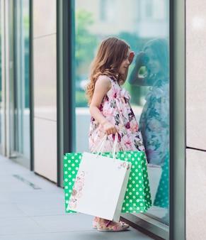 ショッピングセンター近くの窓を見ている少女。
