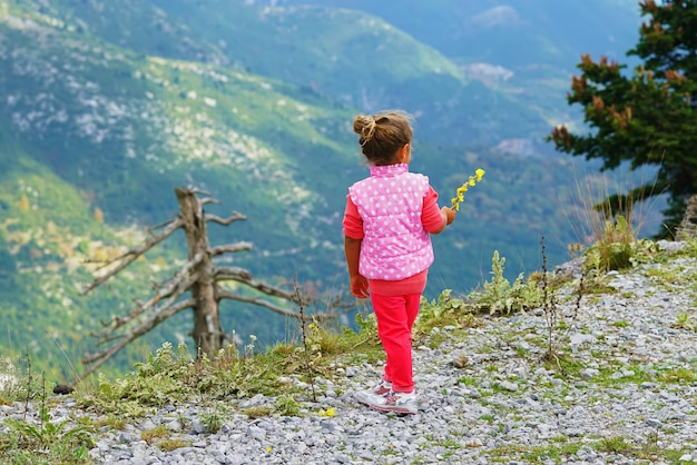 Little girl looks at the mountains