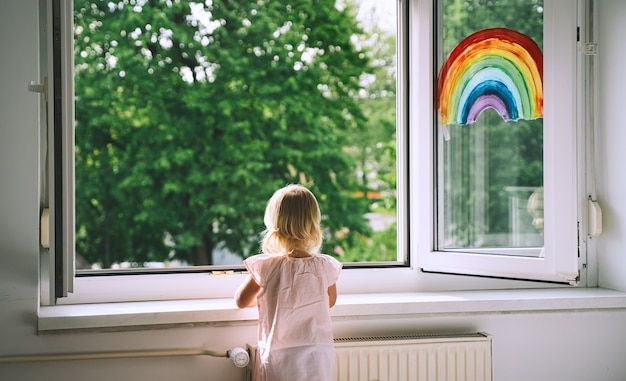 小さな女の子は春に窓の外を見る窓に虹を描く背景にかわいい子供