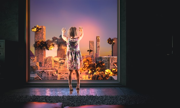 Little girl looks out of the window at a burning city. destroyed buildings, explosions. apocalypse concept.
