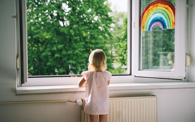 Little girl looks out window at spring time cute child on background of painting rainbow on window
