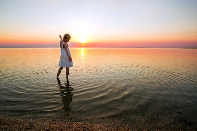 Little girl looks at the sunset at the sea