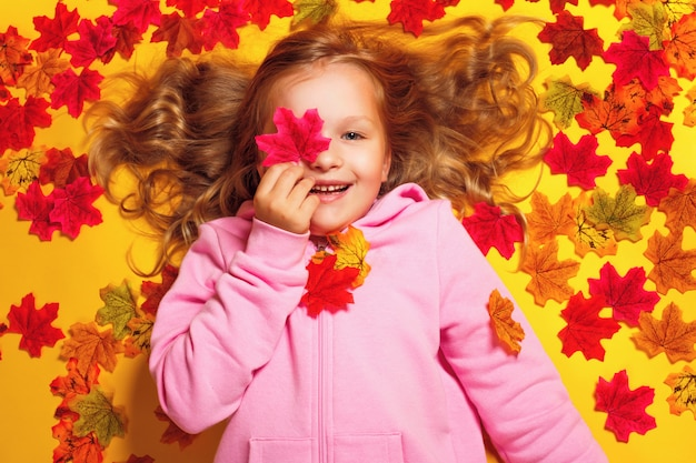 Little girl lying on autumn maple leaves
