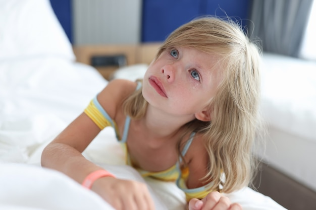 Little girl lying in bed in clinic and crying