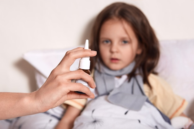 Little girl lying in bed, her mom treating her runny nose with nasal spray, dark haired female child looking at camera