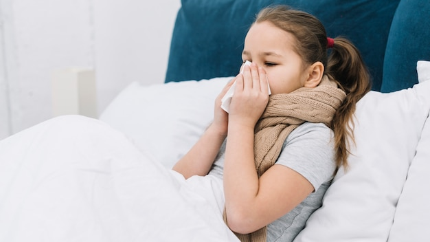 Little girl lying on bed suffering from the cold and cough