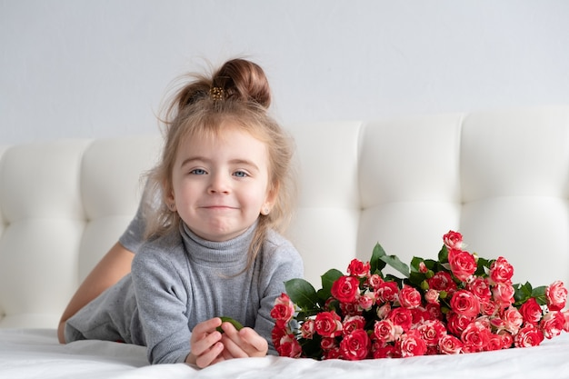 Little girl lying on bed with bouquet of pink roses.